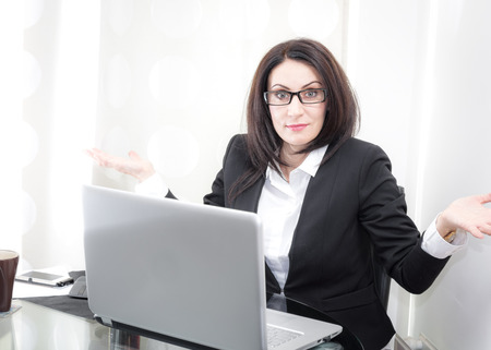shrugs: Confused mature businesswoman wearing glasses shrugs her shoulders in a clueless gesture in front of a laptop computer