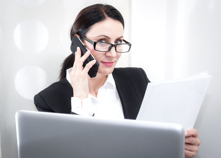 phonecall: Mature brunette businesswoman wearing a suit and glasses is talking on the cell phone while holding a stack of papers and she is in front of the computer.