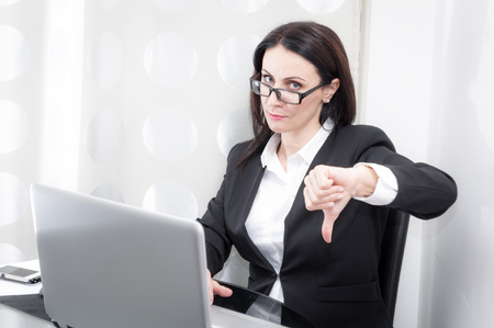 dissatisfaction: Woman working in a office shows the thumbs down gesture expressing her dissatisfaction with a project shown on the computer Stock Photo