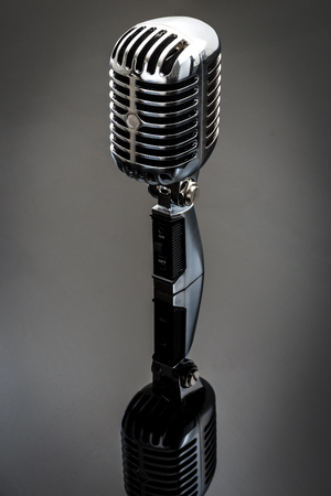 microphone: Retro chrome microphone reflected on a shiny surface Stock Photo