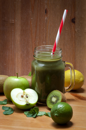 cleanse: Healthy green fruit juice made of kiwi, lemon, lime and green apples with a straw in it on a rustic wooden table