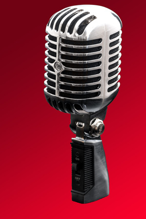 old time: Retro styled chrome microphone isolated on a red background, the kind used in music studios and old time talk shows Stock Photo