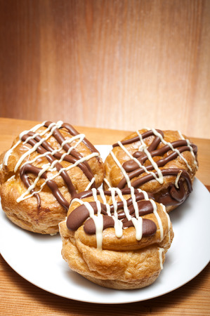 profiterole: Three french choux a la creme on a plate in a rustic kitchen Stock Photo