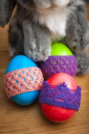 lace like: Bunny holding easter eggs wrapped in knitted lace made to look like sweaters on a rustic wooden background. Easter is the christian holiday when christians celebrate the rebirth of Jesus Christ