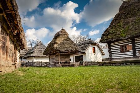 Rustic wooden houses with thatched roofs in a village of rural eastern europe against the blue sky and some clouds in Bucharest, Romania