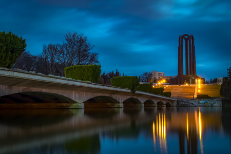 tomb of the unknown soldier: The Mausoleum Of Romanian Heroes (sometimes called the Tomb of the Unknown soldier) was built in 1963 and it is located in Carol Park in Bucharest, Romania on a cloudy night across the bridge Stock Photo