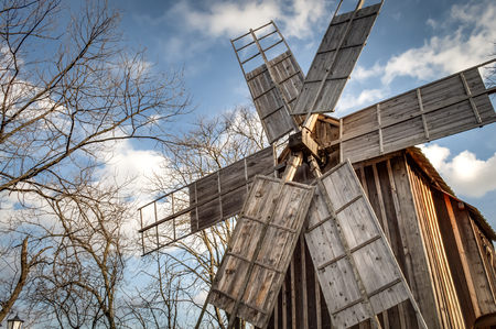 grind: Traditional romanian windmill used by the romanians to grind grains for centuries, against a blue cloudy sky and surrounded by trees