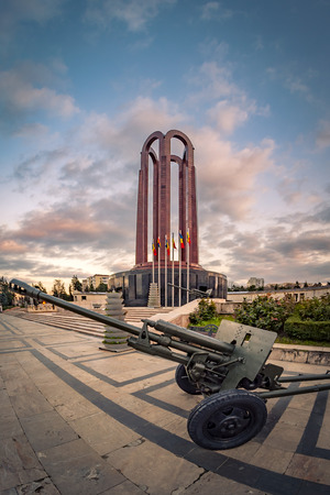 tomb of the unknown soldier: The Mausoleum Of Romanian Heroes (sometimes called the Tomb of the Unknown soldier) was built in 1963 and it is located in Carol Park in Bucharest, Romania with a artillery cannon in the foreground and dramatic clouds in the background