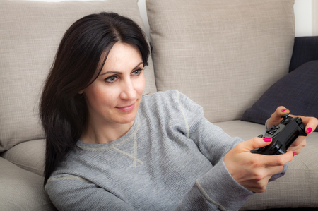 immersed: Mature woman sitting next to the sofa, holding a controller is immersed in the video game she is playing
