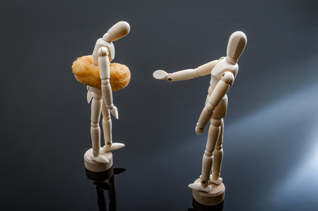 Two human shaped figurines one portrayed as overweight because of a doughnut around the waist and the other pointing at the doughnut illustrating the concepts of bullying and fat shaming Reklamní fotografie