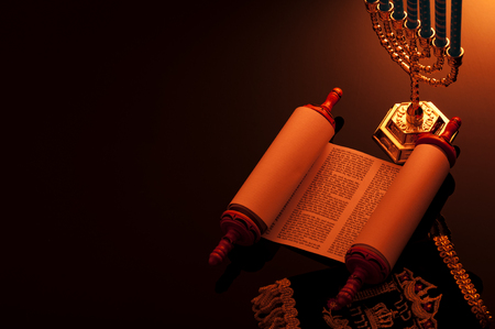 Religion and Judaism concept with candle lit scene of the holy Torah and a menorah with copy space Фото со стока