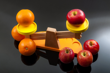 The idiom, comparing apples and oranges, refers to the differences between incomparable or incommensurable items. The concept is illustrated by 2 groups of apples and oranges on a balance scale