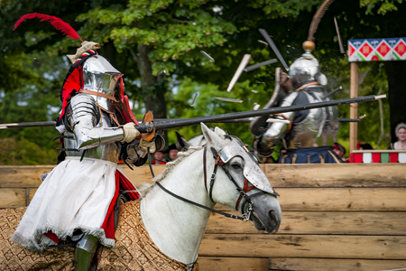 Armored knights on horseback charging in a joust right after the impact . Jousting is a martial game or hastilude between two horsemen wielding lances with blunted tips, often as part of a tournament.