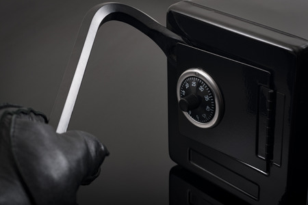 Home invasion and burglary concept with first person view of a burglar wearing black leather gloves while breaking into a safe with a crowbar Reklamní fotografie