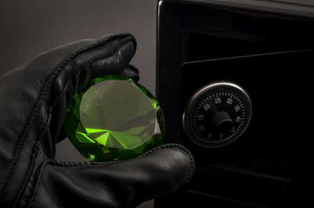Home invasion and burglary concept with hand in leather gloves holding the loot a green saphire
