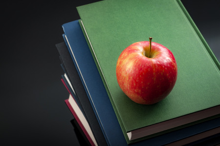 Back to school concept with an apple on top of a stack of books arranged in a tower and copy space