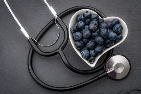 Healthy eating and heart health concept with a heart shaped bowl with blueberries and a stethoscope each blueberry is packed full of vitamins and antioxidants that can prevent coronary heart disease Фото со стока