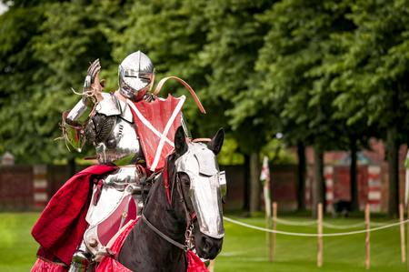 Armored knight suited for battle on horseback, charging in gallop. Galloping it's the fastest gait of a horse, and because of the speed the warrior looks even more impressive Stock Photo