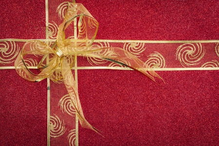 Glitter gift ribbon and bow on red glittery background for Christmas with copy space Фото со стока