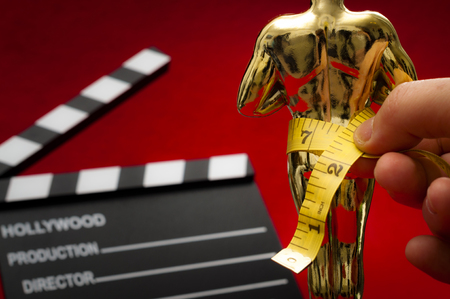 Film and entertainment industry concept with measuring tape around a movie award representing the predisposition    to discriminate against actors and actresses that are not skinny enough