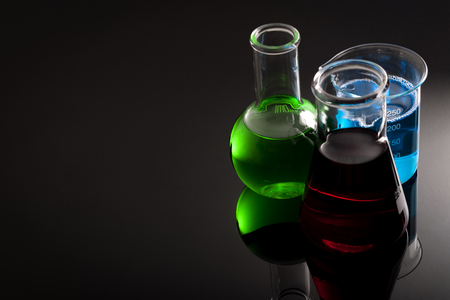 Chemistry laboratory and chemicals concept wit flask, test tube and other lab glassware containing green, red and blue color liquids on dark background with copy space Фото со стока