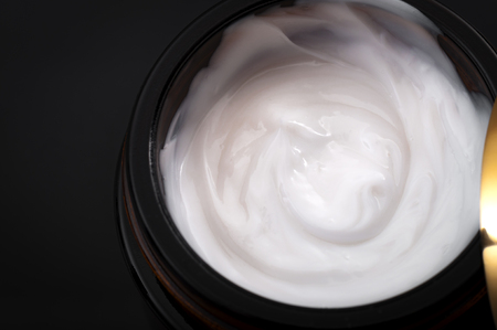 Beauty and cosmetics concept with closeup on a moisturizing cream in an open jar with copy space on a dark background, Close-up and macro photography Фото со стока