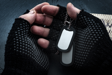 Homeless veterans and social issues concept with grunge image of dirty hands of a homeless man wearing fingerless gloves and holding dog tags Stockfoto