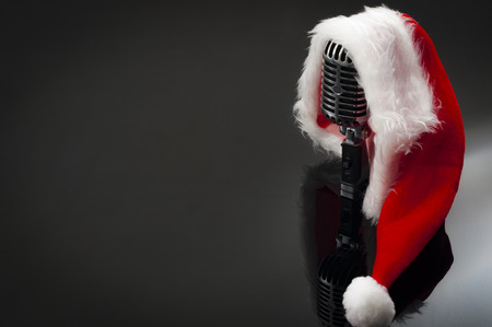 Carols and Christmas music concept with a microphone wearing a santa hat with copy space
