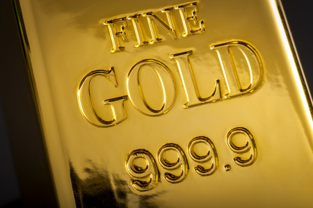 Banking and financial industry concept with closeup on the text that says fine gold 999.9 on one gold bar. Although the gold standard has passed, a declining US dollar means rising gold prices