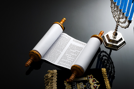 Religion and Judaism concept with the holy Torah and a menorah. The Torah is the jewish holy text  book and a menorah is the traditional branched candle stick specific to Hanukkah Imagens