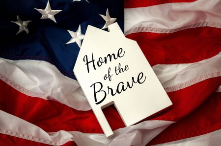 Independence day, land of the free and home of the brave or 4th of July concept theme with a slate in the shape of a house with text and the USA flag