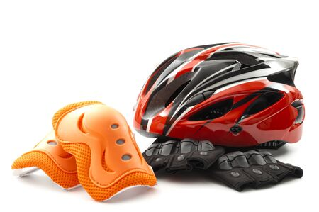 Cycling safety equipment and bicycle riding gear conceptual idea with red bike helmet, fingerless gloves and orange knee pads isolated on white background Stok Fotoğraf