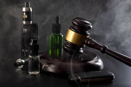 Legal act to restrict vaping, outlaw smoking electronic cigarettes and vape ban legislation conceptual idea with judge gavel, vape device, bottle of ejuice and smoke isolated on black background