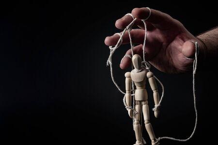 Employeur manipulant l'employé, manipulation émotionnelle et obéissant au concept principal avec une main menaçante tirant les ficelles sur une marionnette avec un contraste maussade sur fond noir avec espace de copie