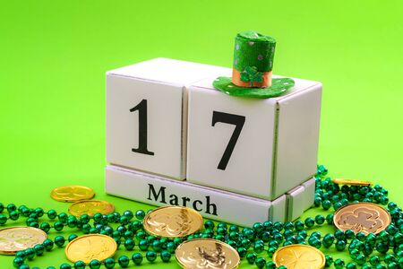 St Patrick's Day meme and Irish spring holiday concept theme with a block calendar showing the date of March 17, leprechaun hat with sparkling clover leaf, shamrock, beads isolated on green background