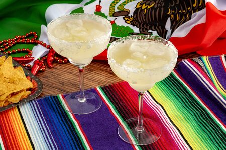 Mixed alcoholic drinks and spirits, patriotic party and mexican fiesta concept theme with two margarita glasses with salted rim, tortilla chips and the flag of Mexico on traditional rug called serape