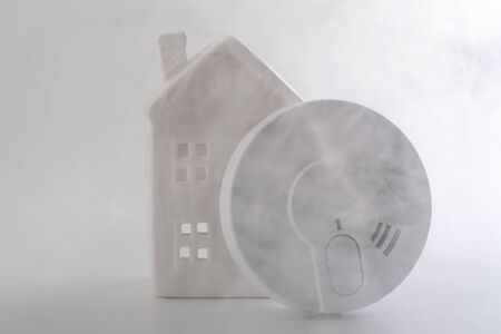 Fire prevention, home security and monitoring dangerous fumes conceptual idea with generic smoke detector and miniature house surrounded by thick smoke isolated on white background Stok Fotoğraf