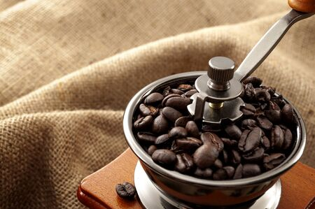 Caffeine rich strong stimulant beverage conceptual idea with detailed close up vintage manual coffee grinder with beans full of flavour isolated on burlap sack background with copy space Reklamní fotografie