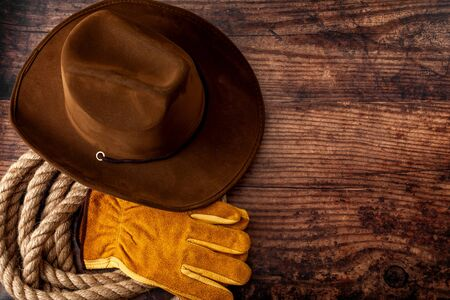 American culture, living on a ranch or farm and country muisc concept theme with a cowboy hat, rope lasso and rodeo leather gloves on a wooden background in a old saloon with copy space Reklamní fotografie