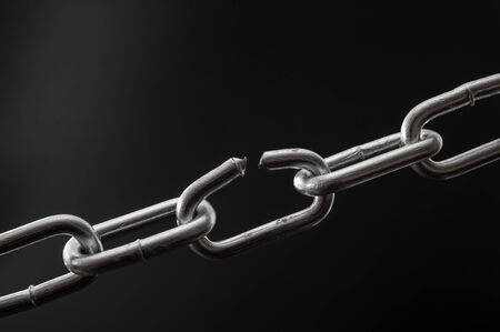 The team is as strong as its weakest link and single point of failure concept with powerful iron chain with one stressed link breaking under physical pressure isolated on black background Banque d'images