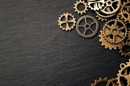 Steampunk accessories and old technology conceptual idea with border made of a group brass cog wheels on dark texture background with copy space