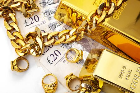 Jewelry buyer, pawn shop and buy and sell precious metals concept theme with pile of cash in british pounds, golden rings, necklace bracelet and gold bullion isolated on white background