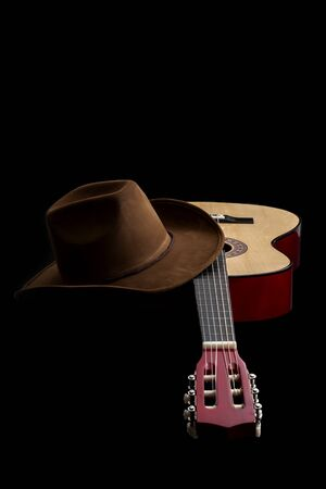 American culture, folk song and country muisc concept theme with a cowboy hat and an acoustic guitar isolated on black background with dramatic lighting