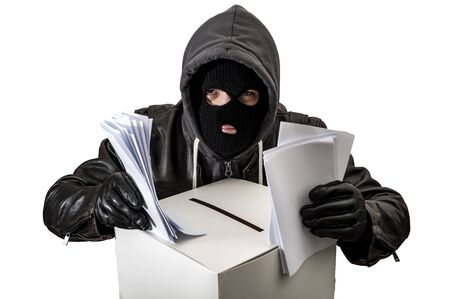 Election fraud and vote rigging concept with a thief wearing a hoodie, ski mask and leather gloves is ballot stuffing an electoral voting box, isolated on white with a clipping path cutout Banque d'images