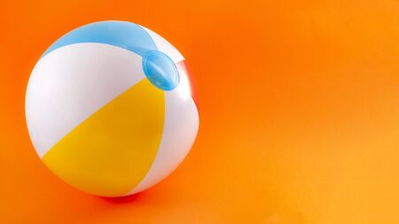 Summer vacation, beach toy and seaside fun activities concept with a inflatable beach ball isolated on orange background with copy space