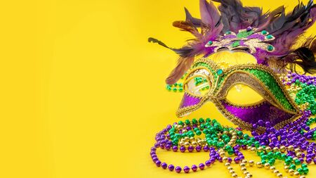 Happy Mardi Gras and Fat Tuesday carnival concept with close up on a face mask full of color, feathers and texture and golden, green and purple beads isolated on yellow background with copy space Stock Photo