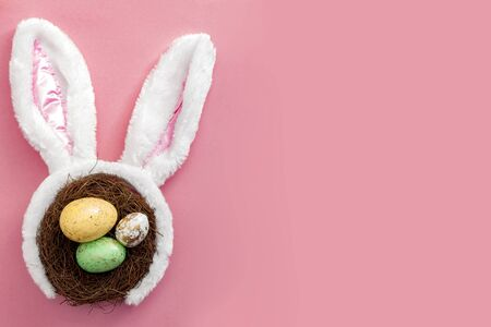 Happy easter and spring meme concept with adorable bunny ears on a bird nest with colorful eggs against a bright pink background with copy space Standard-Bild