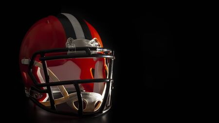 Dark side of college sports concept with high contrast lighting on american football helmet illuminated by dramatic hard light with harsh shadows isolated on black background with copy space Stock Photo