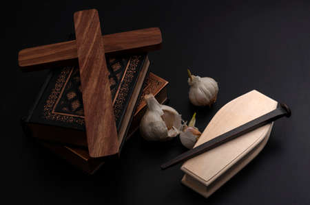 Halloween decoration, Mythology of Transylvania, legend of Dracula and vampire killing kit concept with books, fresh garlic, metal stake, wooden coffin and holly cross on dark background Stock Photo