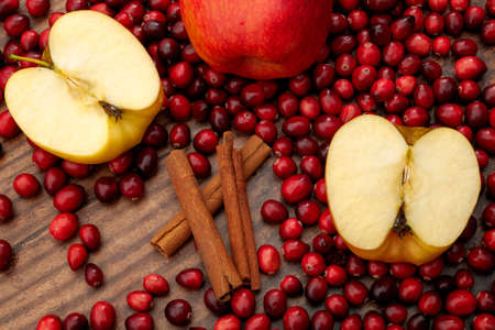 Christmas and holidays recipes, mulled wine ingredients and seasonal cooking concept with sliced red apples, heap of cranberries and cinnamon sticks isolated on wooden background Stockfoto